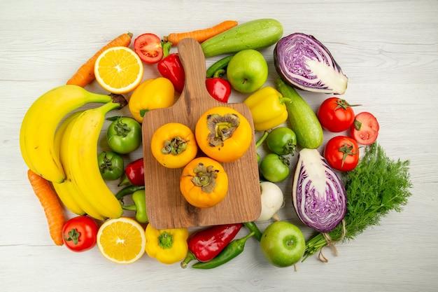 Composizione vegetale vista dall'alto con frutta su sfondo bianco