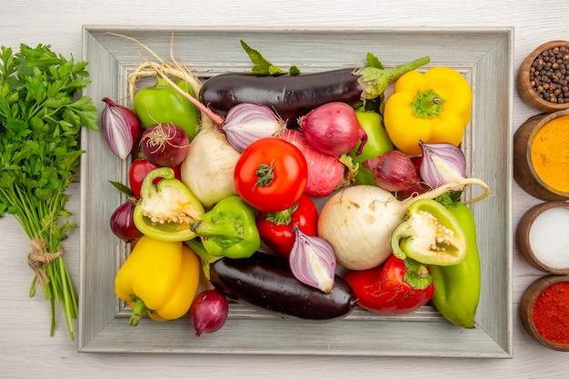 흰색 테이블에 채소와 조미료가 있는 상위 뷰 야채 구성