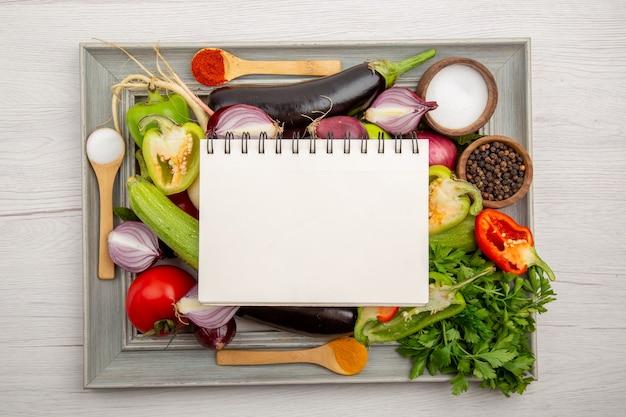 Composizione vegetale vista dall'alto con blocco note verdi e condimenti sul tavolo bianco