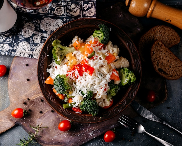 Top view vegetable dish including broccoli red tomatoes and rice on the grey floor
