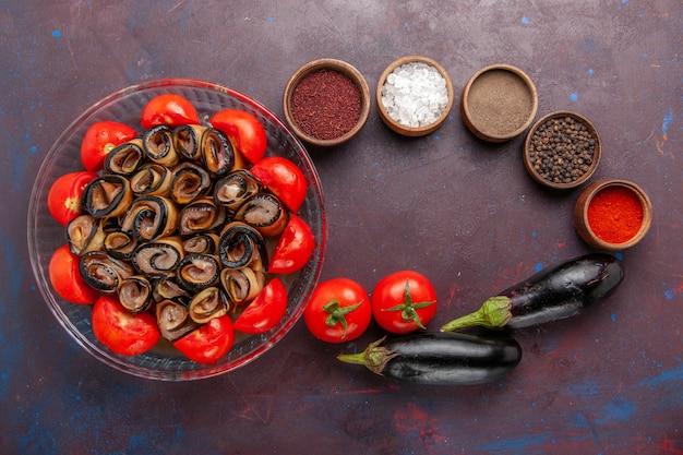 어두운 책상에 가지와 조미료가 들어간 토마토 슬라이스 및 압연 상위 뷰 야채 식사