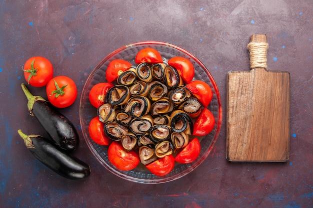 Вид сверху овощной муки, нарезанных и свернутых помидорами с баклажанами на темном фоне