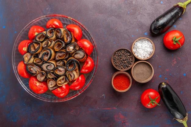 Vista dall'alto di farina di verdure a fette e pomodori arrotolati con melanzane e condimenti su sfondo scuro