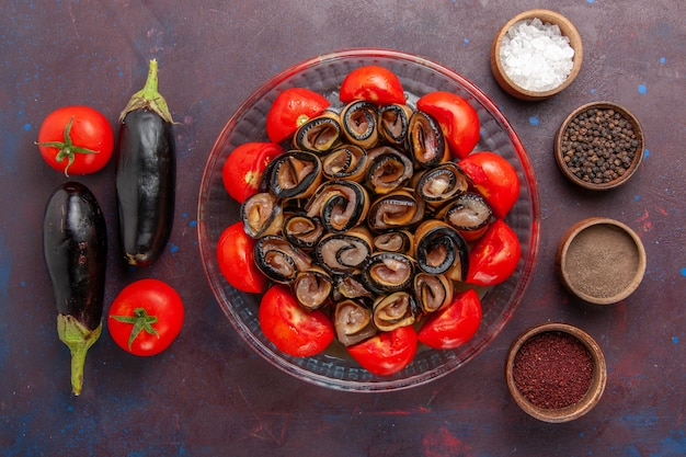 Top view vegetable meal sliced and rolled tomatoes with eggplants and seasonings on dark background