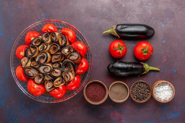 Vista dall'alto di farina di verdure a fette e pomodori arrotolati con melanzane e condimenti sul pavimento scuro