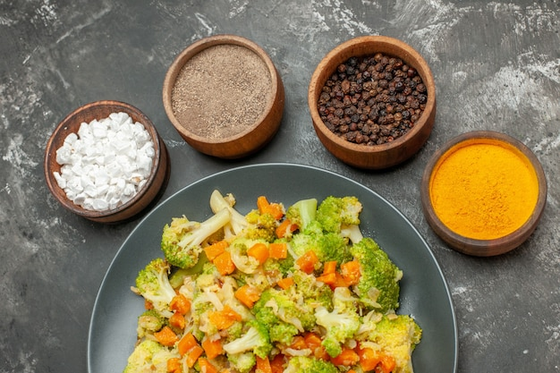 Top view of vegetable meal with brocoli and carrots on a black plate and spices on gray background