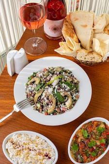 Un pasto di verdure con vista dall'alto con pane di carne e vino sul tavolo durante la cena del pasto diurno