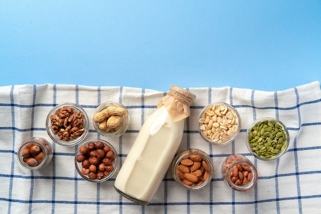 Top view of vegetable milk bottle with bowls of nuts