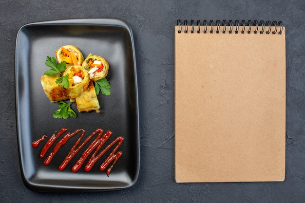 Овощные паштеты, вид сверху, внутри черной тарелки на темной поверхности