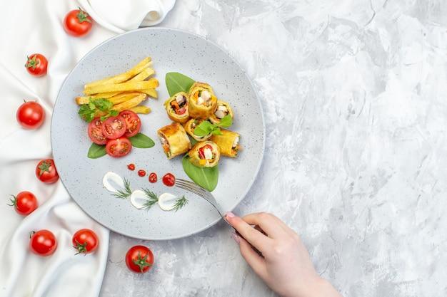 Вид сверху овощные паштеты с помидорами и картофелем фри внутри тарелки на белой поверхности