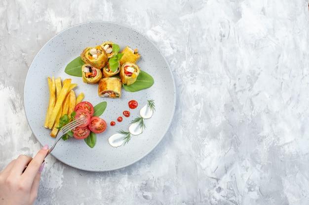 Vista dall'alto patè di verdure rotoli con pomodori e patatine fritte all'interno della piastra sulla superficie bianca