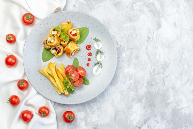 Top view vegetable pate rolls with tomatoes and french fries inside plate on white surface