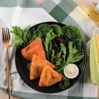 三角形の形をした平面図の野菜リッソール。とうもろこし、にんじん、さやいんげんを詰めた薄いクレープを、新鮮な野菜とマヨネーズを添えた白いプレートに盛り付けました