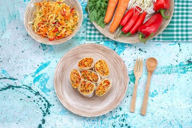 Овощные рулеты, нарезанные вместе со свежим овощным салатом, на ярко-синем столе, овощная еда, салат, вид сверху