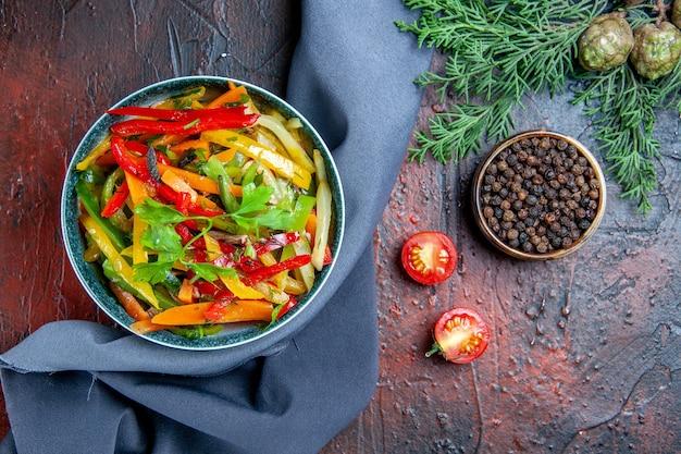 Vista dall'alto insalata di verdure in ciotola pepe nero ramo di abete scialle blu oltremare sul tavolo rosso scuro