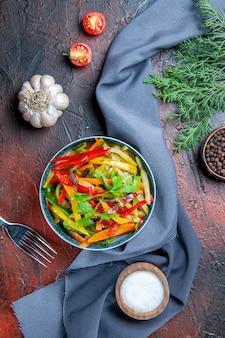 Vista dall'alto di insalata di verdure nella ciotola pepe nero ramo di abete blu oltremare scialle aglio sale sul tavolo rosso scuro