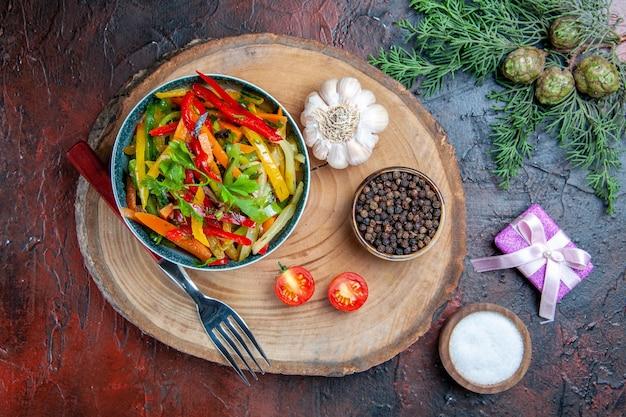 Vista dall'alto di insalata di verdure in ciotola forcella aglio pepe nero sul ramo di abete bordo rustico sulla tavola rosso scuro