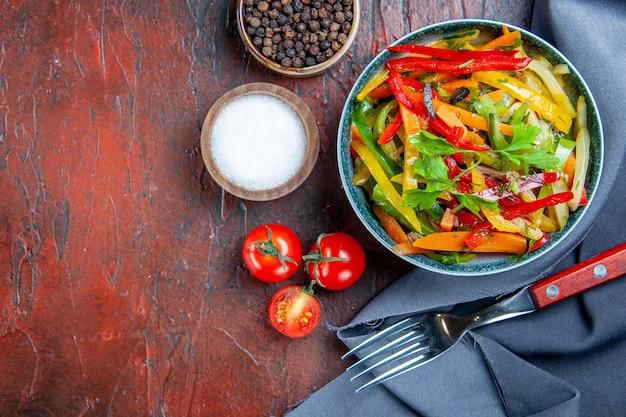 Vista dall'alto insalata di verdure nella ciotola blu oltremare scialle pomodorini spezie forcella sullo spazio libero tavolo rosso scuro