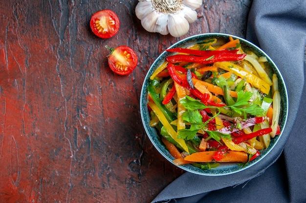 Vista dall'alto insalata di verdure in una ciotola blu oltremare scialle aglio sul posto libero tavolo rosso scuro
