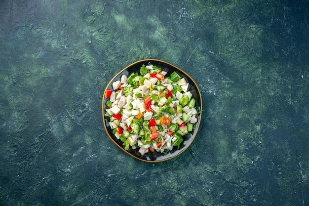 トップビュー野菜サラダは、濃紺の背景色のチーズきゅうりとトマトで構成されています健康ランチ生鮮食品の食事