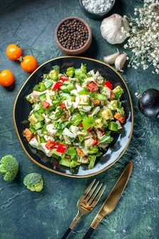 トップビュー野菜サラダは、紺色の背景色のキュウリチーズとトマトで構成されていますダイエット食事料理レストランフードヘルスランチ