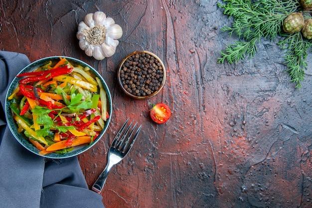 ボウルのトップビュー野菜サラダウルトラマリンブルーショールガーリックブラックペッパーフォークダークレッドテーブルコピー場所
