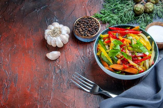 ボウルのトップビュー野菜サラダウルトラマリンブルーショールガーリックブラックペッパーフォークダークレッドテーブル