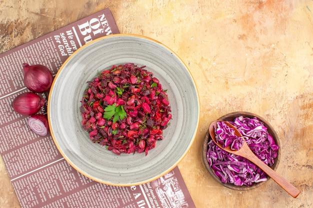 Insalata di verdure vista dall'alto su un grande piatto grigio fatto di cipolle rosse mazzetto di prezzemolo e cavolo rosso tritato su un tavolo di legno con copia posto