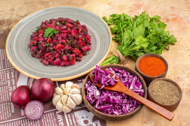 Вид сверху овощной салат на керамической тарелке из красного лука, чеснока, петрушки, черного перца, молотого перца, куркумы и нарезанной красной капусты на деревянном фоне