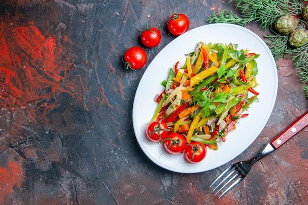楕円形のプレートに野菜サラダの上面図濃い赤のテーブルのコピースペースにチェリートマトのフォーク