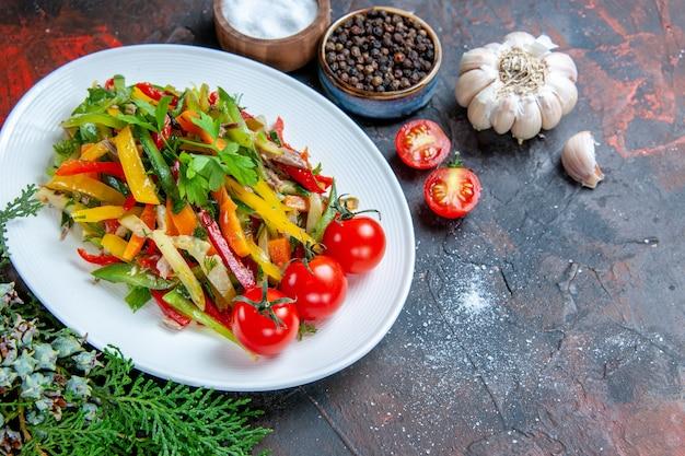 Вид сверху овощной салат на овальной тарелке, помидоры черри, чеснок, специи на темно-красном столе