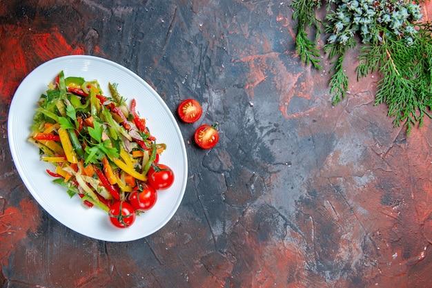 濃い赤のテーブルのない場所に楕円形のプレートチェリートマトのトップビュー野菜サラダ