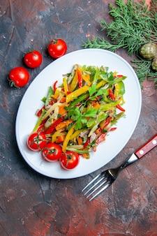 楕円形のプレートフォークチェリートマトの上面図野菜サラダ濃い赤のテーブル