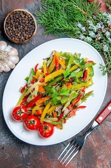 Вид сверху овощной салат на овальной тарелке, вилка, чеснок, черный перец на темно-красном столе
