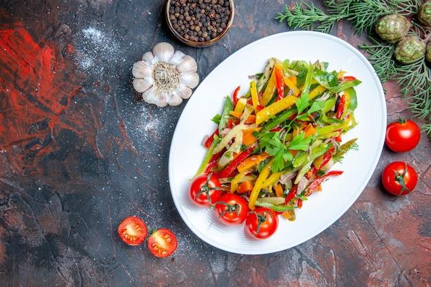 楕円形のプレートにトップビュー野菜サラダガーリックチェリートマトダークレッドテーブルに黒胡椒