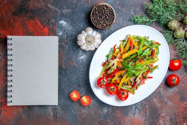 楕円形のプレートのメモ帳にトップビュー野菜サラダ濃い赤のテーブルに黒胡椒にんにくのメモ帳