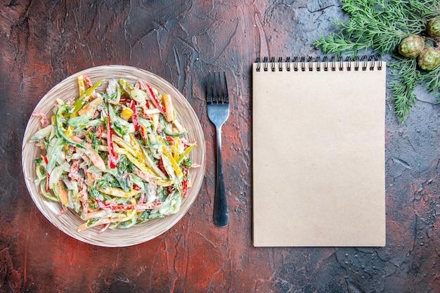 Вид сверху овощной салат на тарелке, вилке, блокноте на темно-красном столе