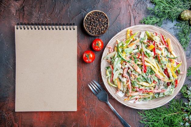 Вид сверху овощной салат на тарелке, вилка, помидоры, черный перец, ветки сосны, блокнот на темно-красном столе