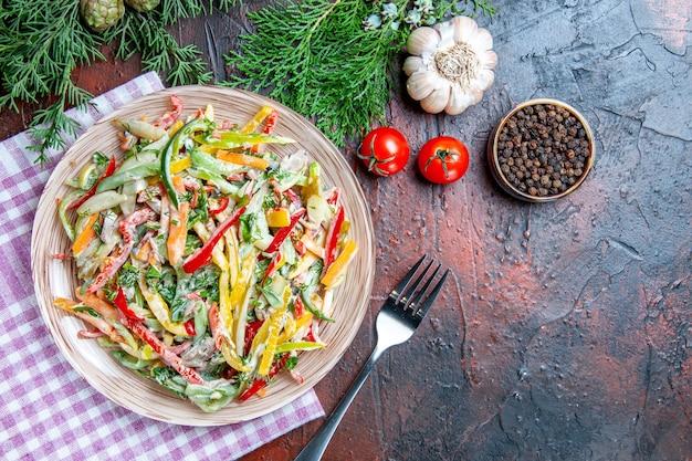 テーブルクロスフォーク黒胡椒トマトニンニクのプレートに濃い赤のテーブルの上のビュー野菜サラダ