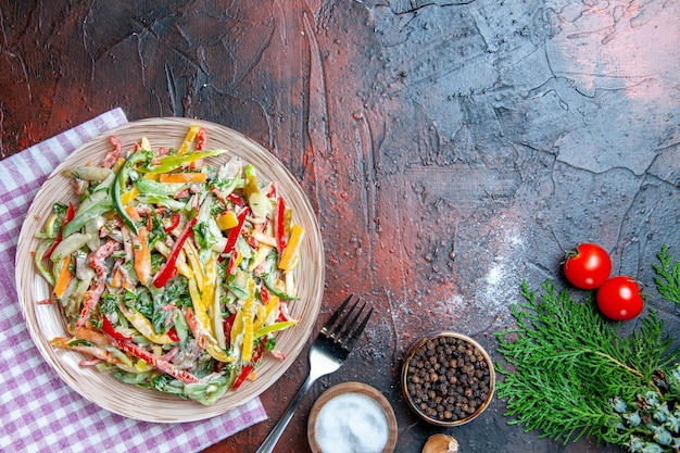 テーブルクロスフォークソルトのプレート上のトップビュー野菜サラダと濃い赤のテーブルの空きスペースに黒胡椒にんにくトマト
