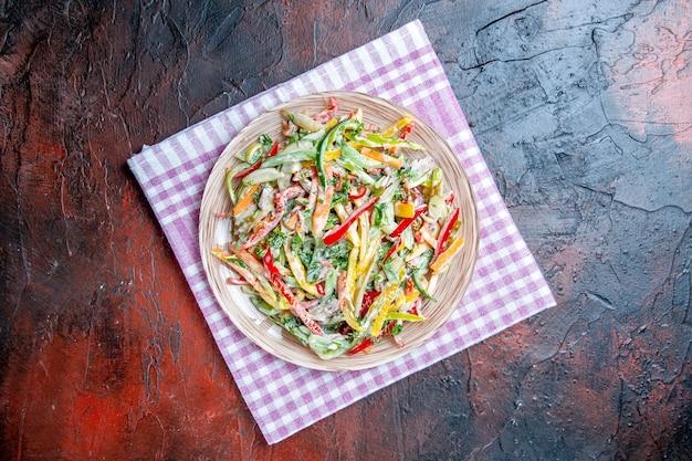 濃い赤のテーブルコピーの場所のテーブルクロスのプレート上のトップビュー野菜サラダ