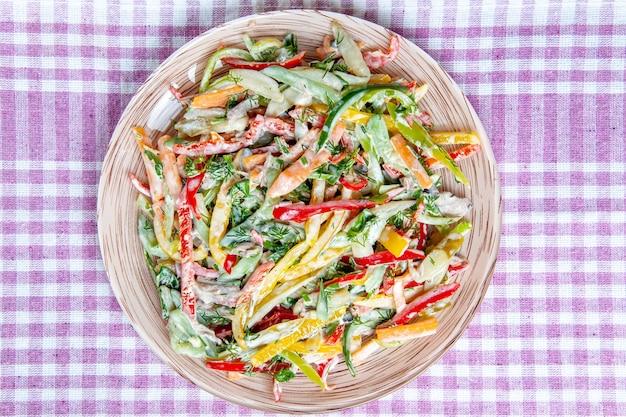 濃い赤のテーブルのテーブルクロスのプレート上のトップビュー野菜サラダ