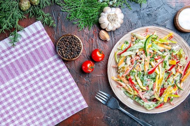プレートテーブルクロスフォークソルトのトップビュー野菜サラダとダークレッドテーブルの黒胡椒にんにくトマト