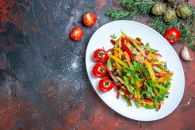Top view vegetable salad on oval plate cherry tomatoes on dark red table copy space