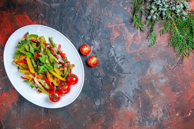 Top view vegetable salad on oval plate cherry tomatoes on dark red table free place