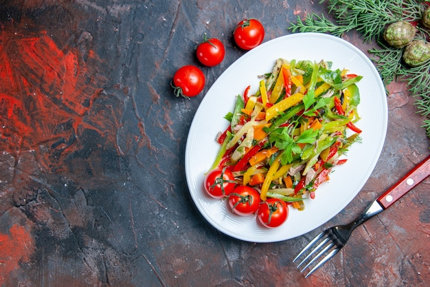 Top view vegetable salad on oval plate cherry tomatoes fork on dark red table copy space
