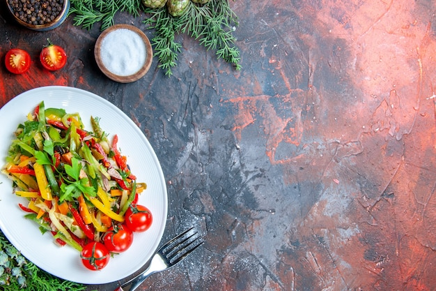 Top view vegetable salad on oval plate cherry tomatoes fork salt on dark red table copy space