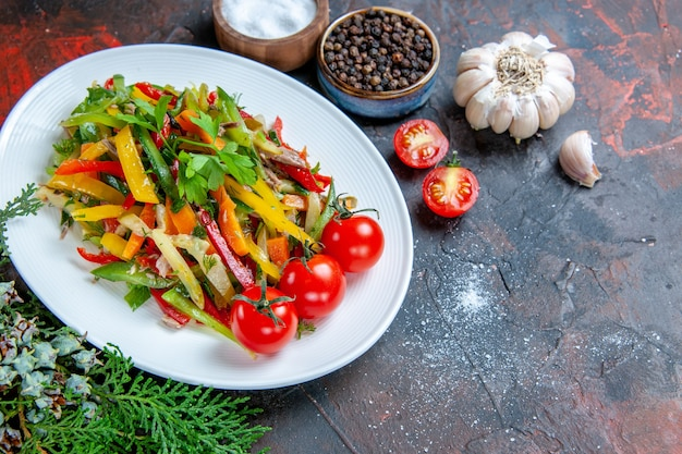Vista dall'alto insalata di verdure sul piatto ovale pomodorini aglio spezie sul tavolo rosso scuro
