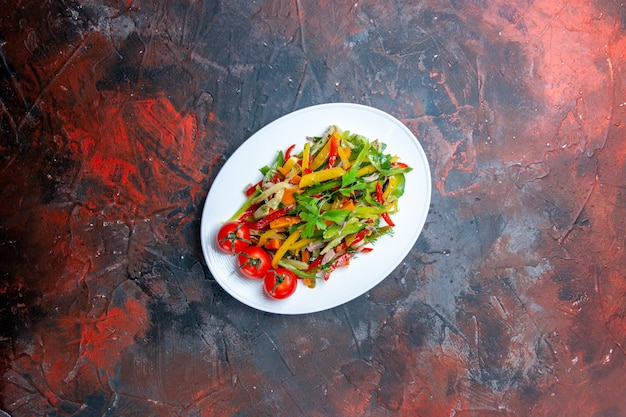 Top view vegetable salad on oval plate on dark table free space