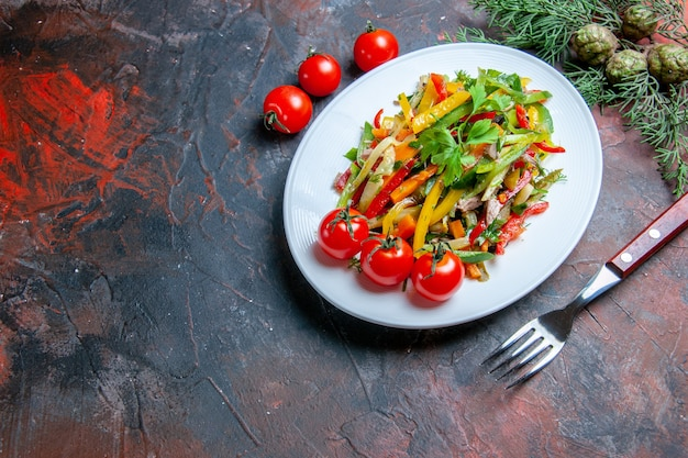 Top view vegetable salad on oval plate fork cherry tomatoes on dark red table